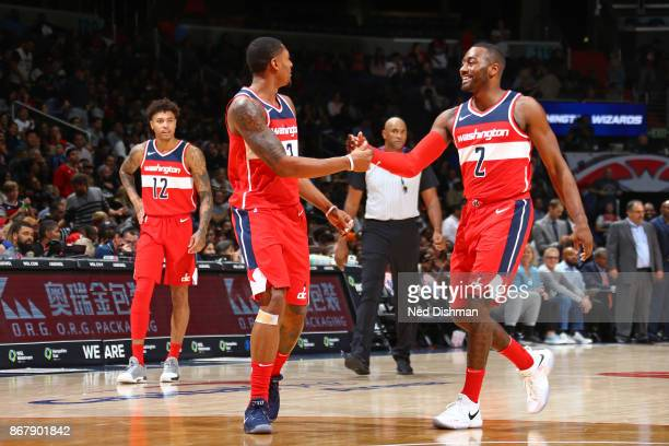 John Wall and Bradley Beal of the Washington Wizards high five during the game against the Detroit Pistons on October 20 2017 at Capital One Arena in...