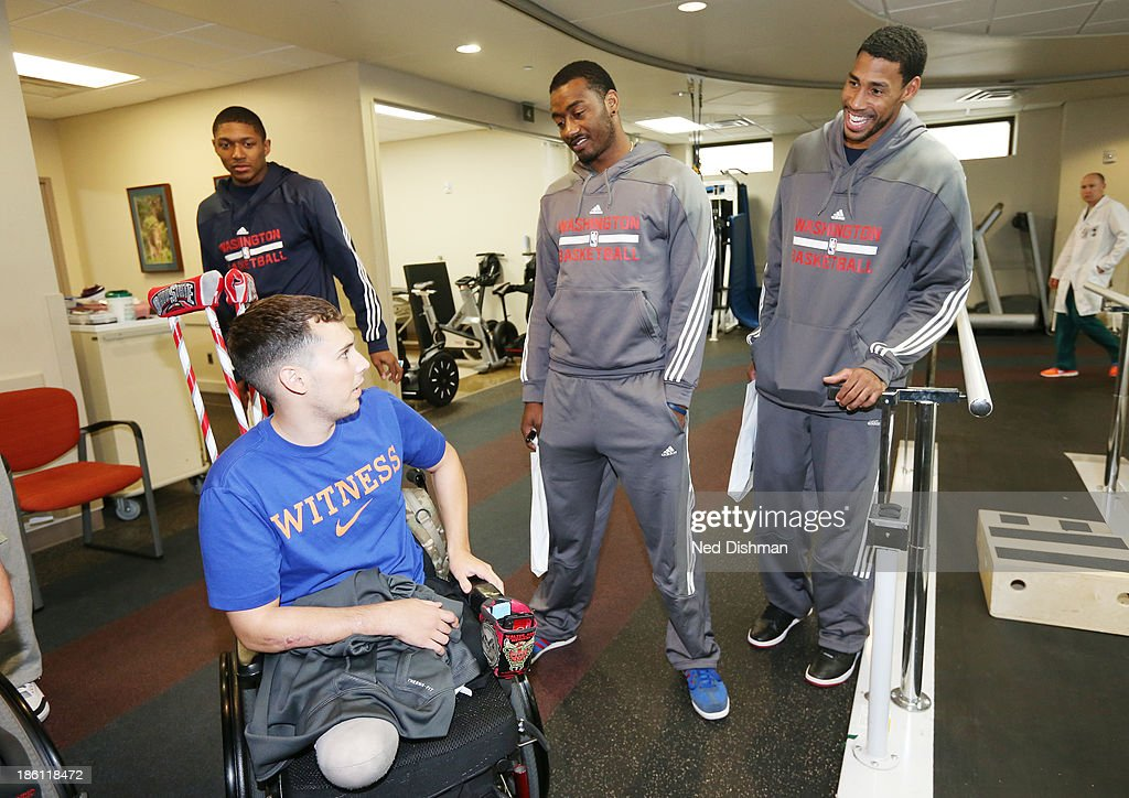 John Wall #2, Bradley Beal #3 and Garret Temple #17 of the Washington Wizards greet a wounded warrior during a visit to Walter Reed Medical Center on October 25, 2013 in Washington, DC.