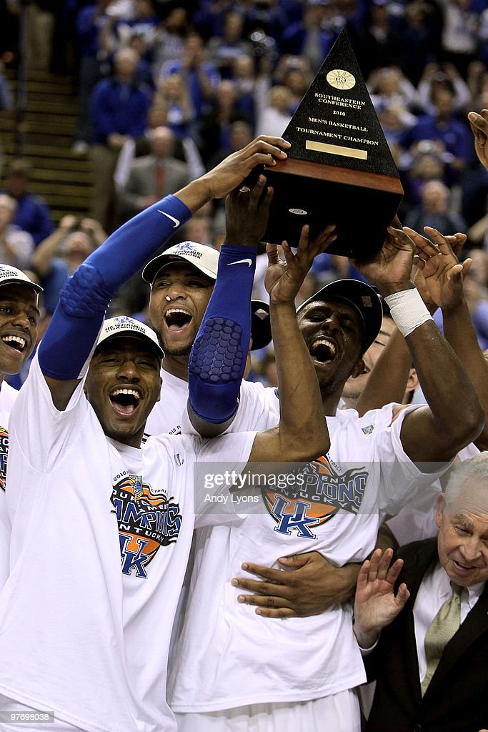 John Wall #11, DeMarcus Cousins #15 and Patrick Patterson #54 of the Kentucky Wildcats celebrate with the trophy along with his teammates after they won 75-74 in overtime against the Mississippi State Bulldogs during the final of the SEC Men's Basketball Tournament at the Bridgestone Arena on March 14, 2010 in Nashville, Tennessee.