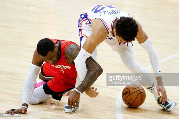 John Wall of the Houston Rockets and Matisse Thybulle of the Philadelphia 76ers reach for a loose ball during the fourth quarter at Wells Fargo...