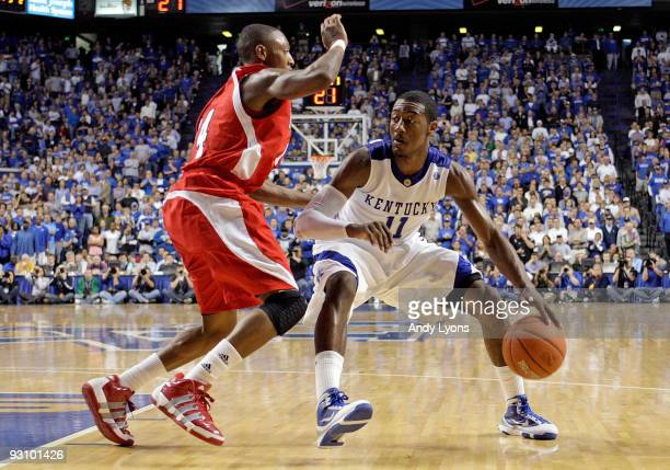 John Wall of the Kentucky Wildcats dribbles the ball while defended by Kenny Hayes of the Miami University Redhawks during the game at Rupp Arena on...