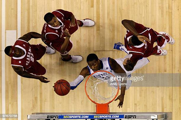 John Wall of the Kentucky Wildcats drives for a shot attempt against Senario Hillman Mikhail Torrance and Jamychal Green of the Alabama Crimson Tide...