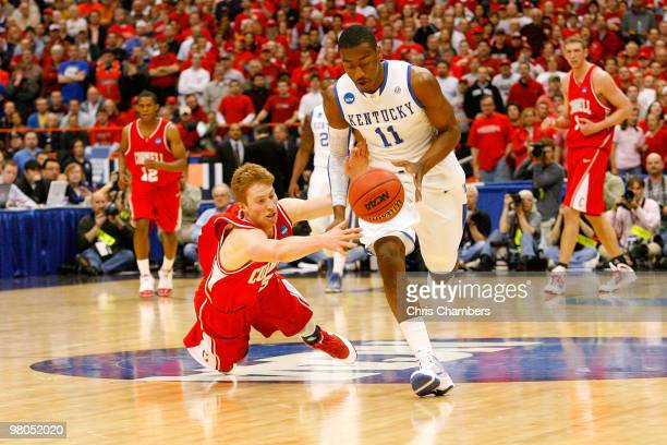 John Wall of the Kentucky Wildcats fights for a loose ball against Chris Wroblewski of the Cornell Big Red during the east regional semifinal of the...
