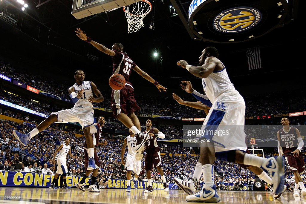John Wall #11 of the Kentucky Wildcats passes the ball to Patrick Paterson #54 against Jarvis Varnado #32 of the Mississippi State Bulldogs during the final of the SEC Men's Basketball Tournament at the Bridgestone Arena on March 14, 2010 in Nashville, Tennessee.