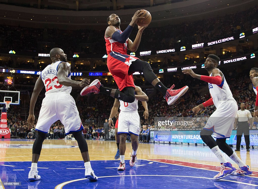 John Wall #2 of the Washington Wizards attempts a layup with Jason Richardson #23 and Nerlens Noel #4 of the Philadelphia 76ers defending on the play on February 27, 2015 at the Wells Fargo Center in Philadelphia, Pennsylvania.