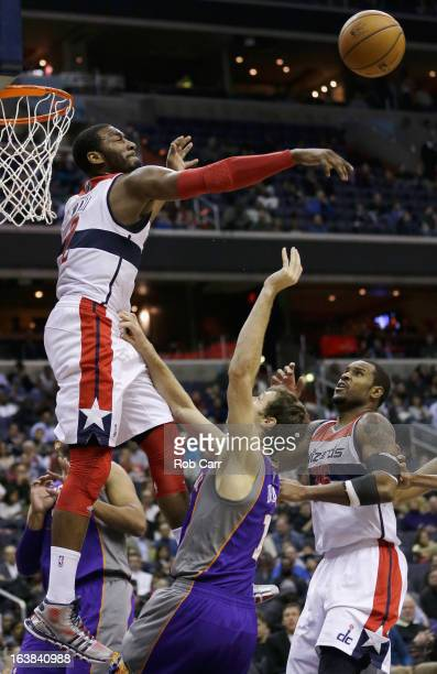 John Wall of the Washington Wizards blocks a shot by Goran Dragic of the Phoenix Suns as teammate Trevor Booker looks on during the second half at...