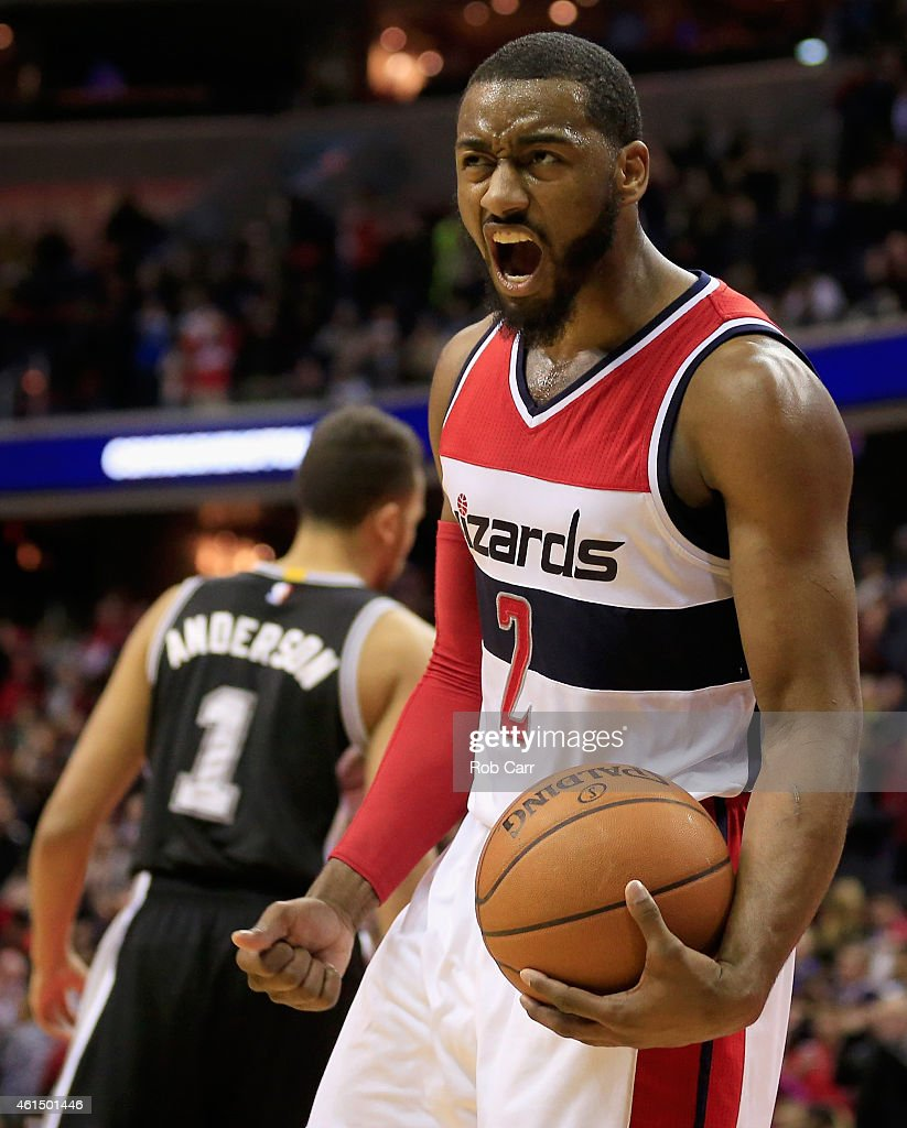 John Wall #2 of the Washington Wizards celebrates in front of Kyle Anderson #1 of the San Antonio Spurs after the Wizards defeated the Spurs 101-93 at Verizon Center on January 13, 2015 in Washington, DC.