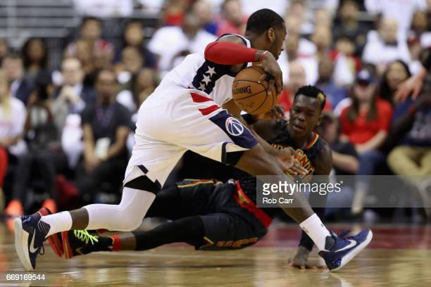 John Wall of the Washington Wizards dribbles the ball around Dennis Schroder of the Atlanta Hawks in the second half in Game One of the Eastern...