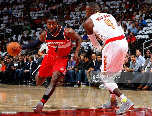John Wall of the Washington Wizards drives against Paul Millsap of the Atlanta Hawks at Philips Arena on October 27 2016 in Atlanta Georgia NOTE TO...
