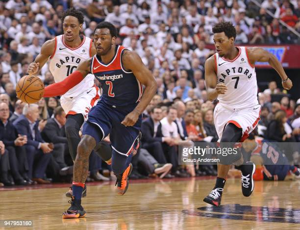 John Wall of the Washington Wizards drives the ball between DeMar DeRozan and Kyle Lowry of the Toronto Raptors in Game Two of the Eastern Conference...