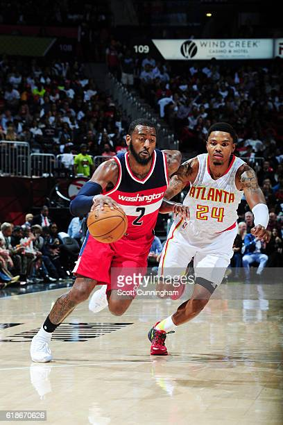 John Wall of the Washington Wizards drives to the basket against Kent Bazemore of the Atlanta Hawks on October 27 2016 at Philips Arena in Atlanta...