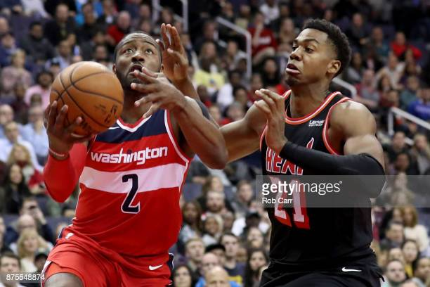 John Wall of the Washington Wizards drives to the basket against Hassan Whiteside of the Miami Heat in the second half at Capital One Arena on...