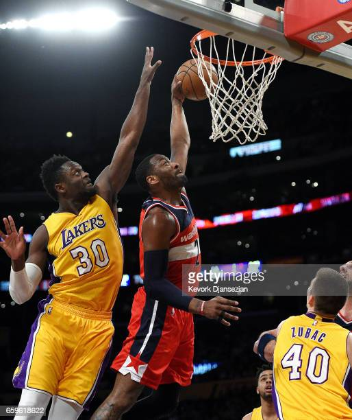 John Wall of the Washington Wizards elevates for a dunk against Julius Randle of the Los Angeles Lakers during the first half of the basketball game...