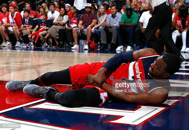 John Wall of the Washington Wizards grabs his wrist after missing a basket and landing on the floor against the Atlanta Hawks during Game One of the...