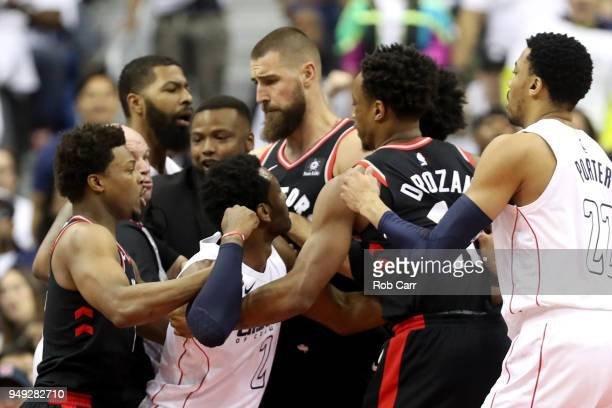 John Wall of the Washington Wizards is separated by players during the first half against the Toronto Raptors during Game Three of Round One of the...