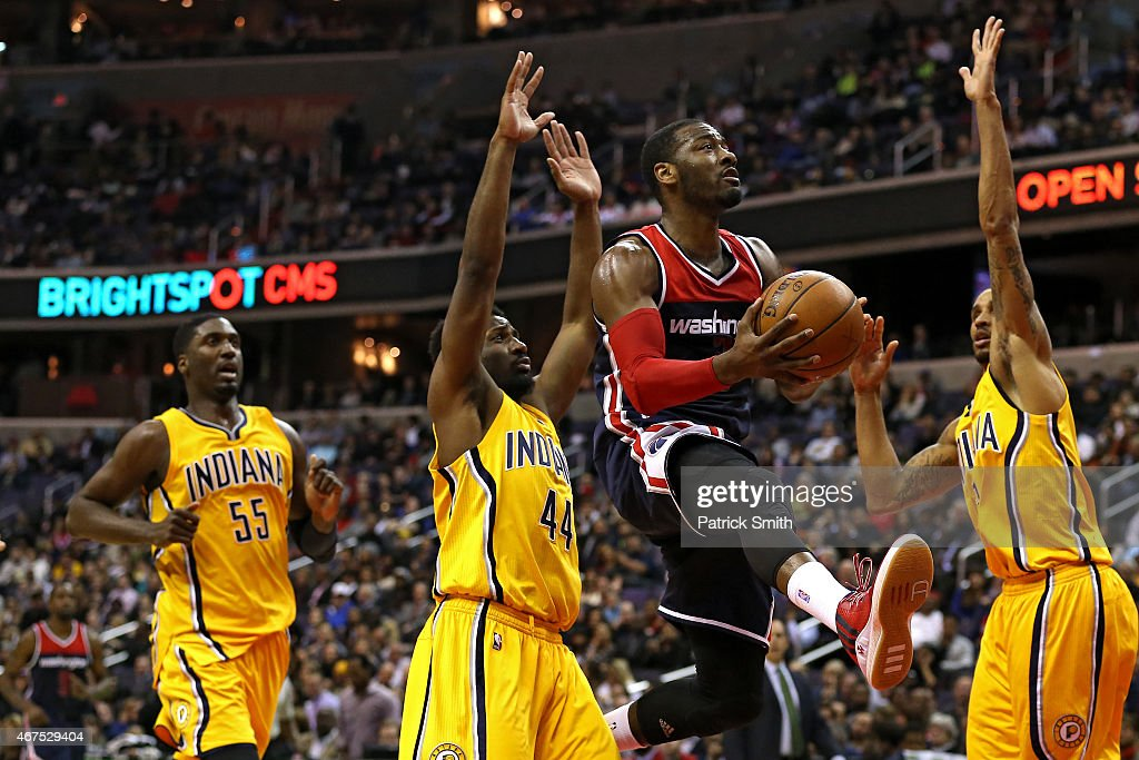 John Wall #2 of the Washington Wizards puts up a shot between Solomon Hill #44 and George Hill #3 of the Indiana Pacers in the first half at Verizon Center on March 25, 2015 in Washington, DC.