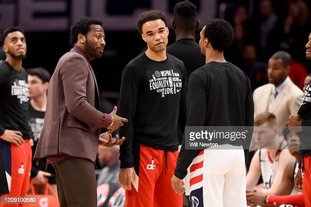John Wall of the Washington Wizards speaks with Jerome Robinson and Ish Smith of the Washington Wizards during a break in play against the Brooklyn...