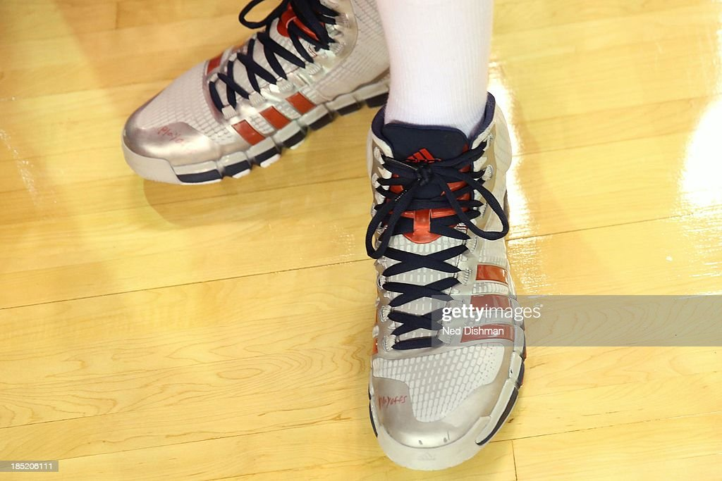 John Wall #2 of the Washington Wizards writes 'playoffs' on his sneakers against the New York Knicks during the pre-season game at the Baltimore Arena on October 17, 2013 in Baltimore, MD.