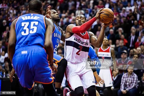 John Wall of Washington Wizard in action against Dion Waiters and Kevin Durant of Oklahoma City Thunders during an NBA game at the Verizon Center in...