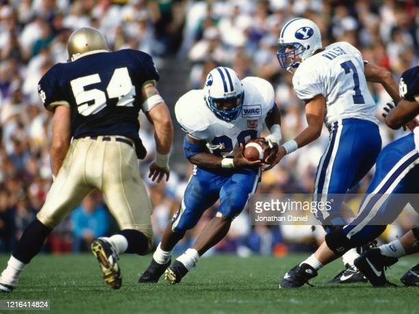 John Walsh, Quarterback for the Brigham Young University Cougars hands the ball off to Running Back Jamal Willis during the NCAA Big Ten Conference...