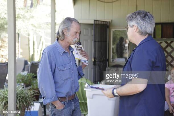 John Walsh speaks with Edgar Schrock of MoveOn canvass for Ann Kirkpatrick on November 3 2018 in Tucson Arizona