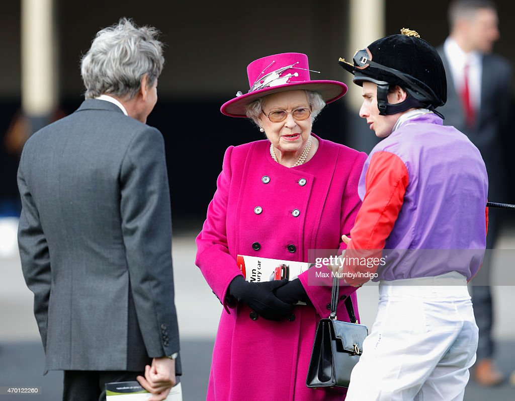 John Warren (Queen Elizabeth II's racing manager) looks on as Queen Elizabeth II talks with jockey Ryan Moore during the Dubai Duty Free Spring Trials Meeting at Newbury Racecourse on April 17, 2015 in Newbury, England.