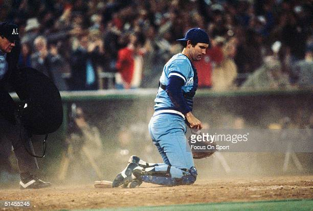 John Wathan catcher for the Kansas City Royals sits in a cloud of dust after the Philadelphia Phillies score two runs during the World Series at...