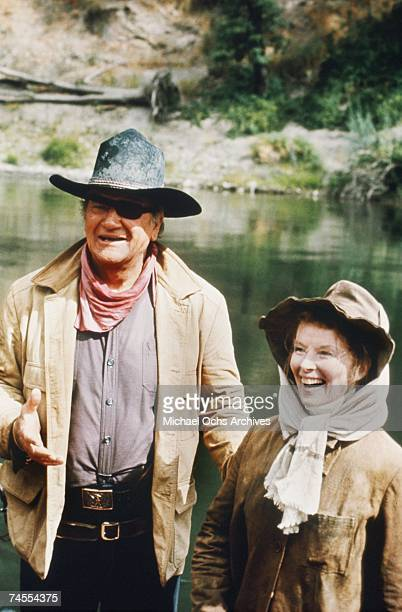 John Wayne and Katharine Hepburn on the set of Rooster Cogburn directed by Henry Hathaway circa 1975 at the Rogue River in the counties of Josephine...
