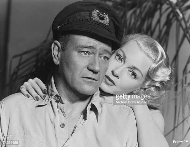 John Wayne and Lana Turner on the set of The Sea Chase directed by John Farrow circa 1955 in Los Angeles California