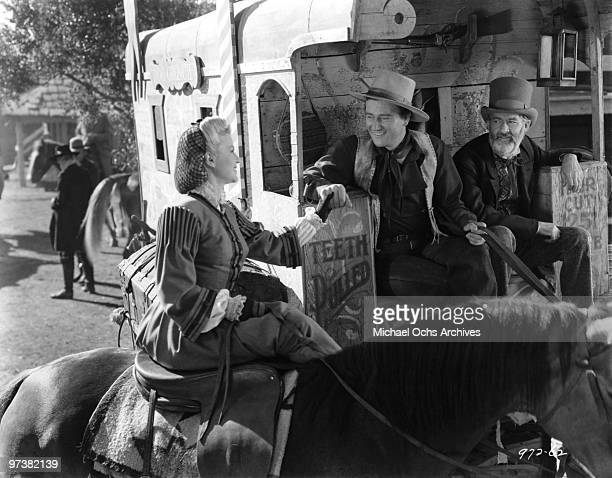 John Wayne Claire Trevor and George 'Gabby' Hayes on the set of the movie 'Dark Command' in 1939 at the Placerita Ranch in Newhall California