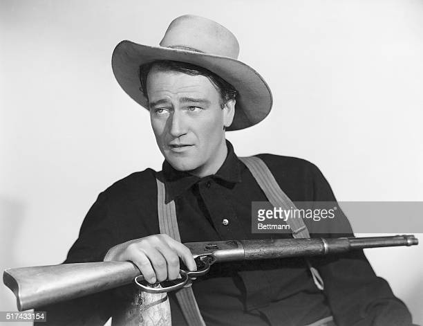 John Wayne holding a rifle in a publicity photo for the movie Shepherd of the Hills