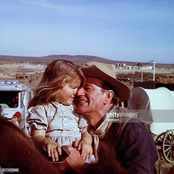 "John Wayne hugs his daughter, Aissa, on the set of The Alamo at the ""Happy"" Shahan Ranch. | Location: Near Brackettville, Texas, USA."