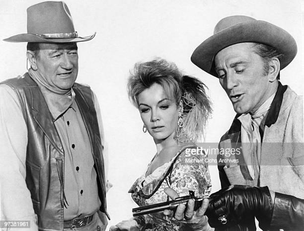 John Wayne Joanna Barnes and Kirk Douglas on the set of 'The War Wagon' in 1967 in Durango Mexico
