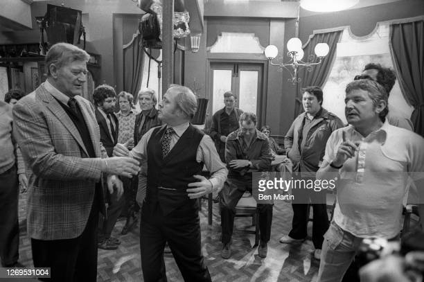 John Wayne on the set of Brannigan with director Richard Attenborough , filmed in London, England, 1974.