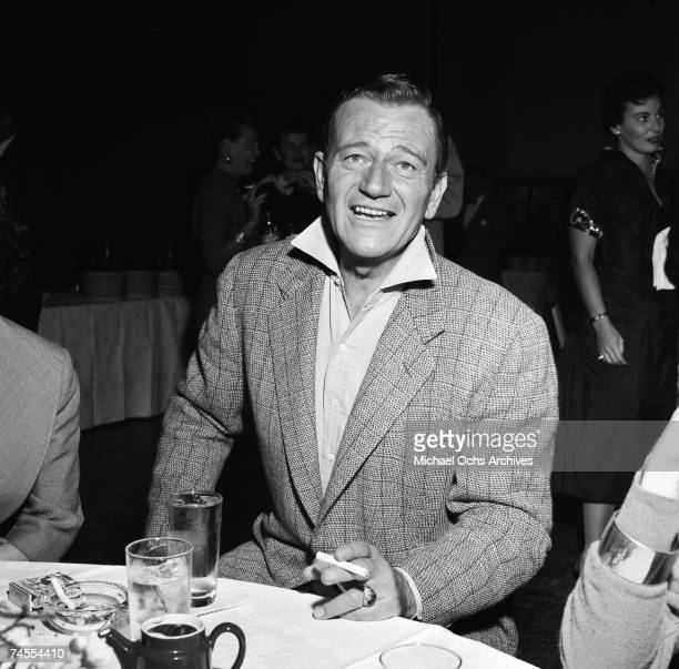 John Wayne smokes a cigarette at a party for Milton Berle on September 26 1955 in Los Angeles, California.