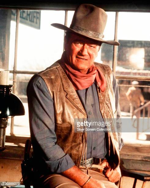 John Wayne US actor wearing a cowboy hat a red neckerchief a blue shirt and a leather waistcoat in a publicity portrait issued for the film 'Chisum'...