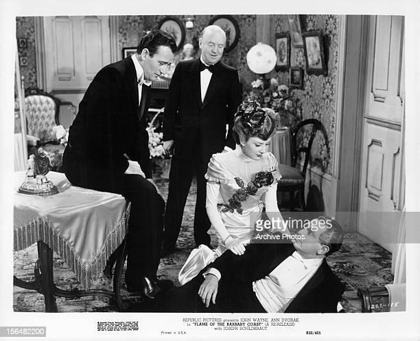 John Wayne watches as Ann Dvorak helps up Joseph Schildkraut in a scene from the film 'Flame Of Barbary Coast' 1945