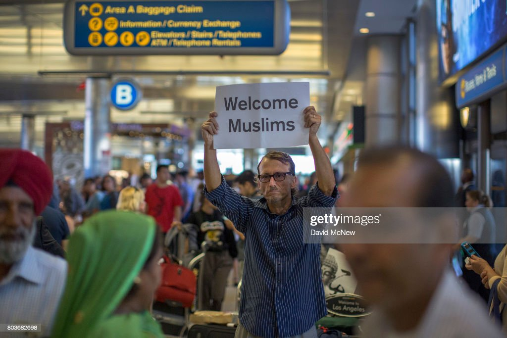 John Wider carries a welcome sign near arriving Sikh travelers on the first day of the the partial reinstatement of the Trump travel ban, temporarily barring travelers from six Muslim-majority nations from entering the U.S., at Los Angeles International Airport (LAX) on June 29, 2017 in Los Angeles, California. Under a Supreme Court order, foreigners who do not have a so-called 'bona fide relationship' with a person or entity in the United States can be banned. The ban effects travelers from Iran, Libya, Somalia, Sudan, Syria and Yemen.