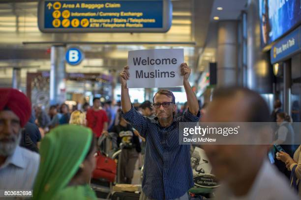 John Wider carries a welcome sign near arriving Sikh travelers on the first day of the the partial reinstatement of the Trump travel ban, temporarily...