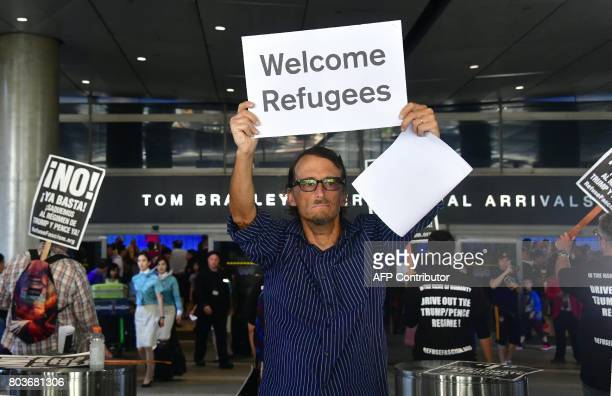John Wider holds a sign that reads 'Welcome Refugees' on one side and 'Welcome Muslims' on the other as he walks the International Arrivals section...