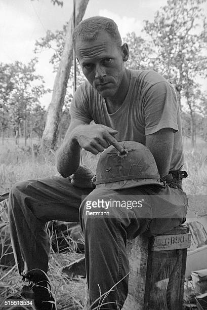 John Wiest of the US 1st Cavalry shows where a Viet Cong bullet pierced his steel helmet while pinned down by Communist fire near Plei Me November...