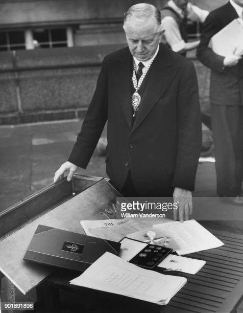 John William Bowen chairman of the London County Council inspects a collection of objects to be placed in a lead casket and buried beneath the...