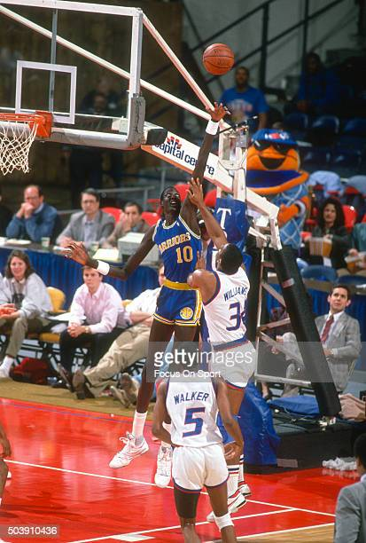 John Williams of the Washington Bullets shoots over Manule Bol of the Golden State Warriors during an NBA basketball game circa 1989 at the Capital...