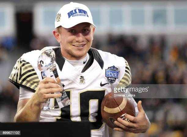 John Wolford of the Wake Forest Demon Deacons celebrates with the MVP trophy after defeating the Texas AM Aggies 5552 after the Belk Bowl at Bank of...