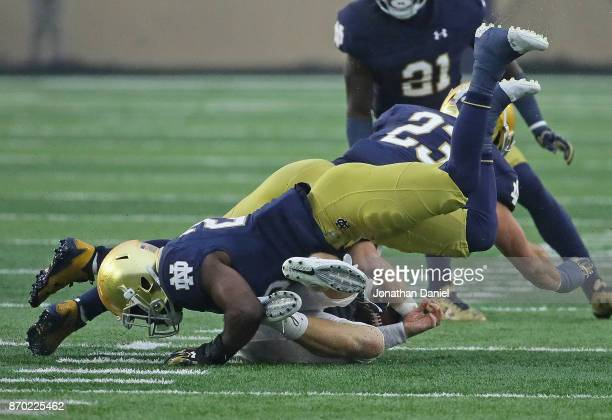John Wolford of the Wake Forest Demon Deacons is flattened by Shaun Crawford and Drue Tranquill of the Notre Dame Fighting Irish at Notre Dame...