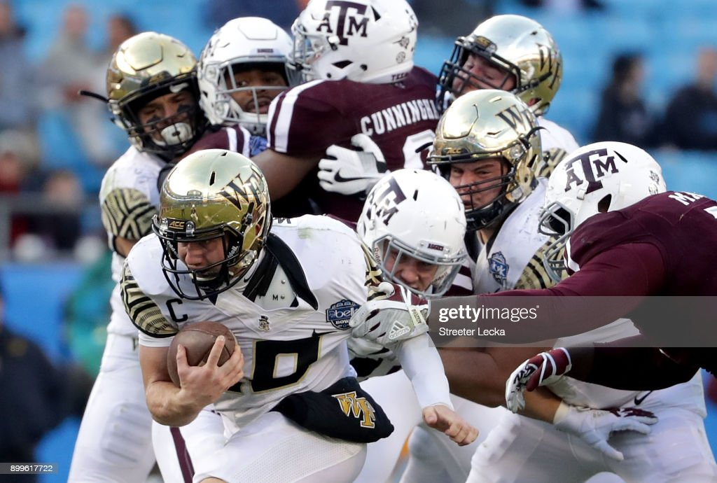 John Wolford #10 of the Wake Forest Demon Deacons runs with the ball against the Texas A&M Aggies during the Belk Bowl at Bank of America Stadium on December 29, 2017 in Charlotte, North Carolina.