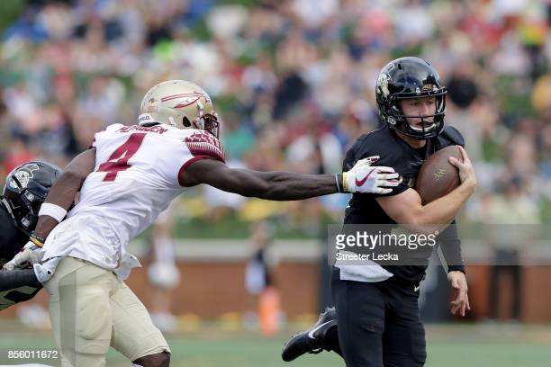 John Wolford of the Wake Forest Demon Deacons tries to get away from Tarvarus McFadden of the Florida State Seminoles during their game at BBT Field...