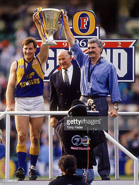 John Worsfold and Mick Malthouse of the Eagles holds aloft the premiership trophy after winning the AFL Grand Final match between the Geelong Cats...