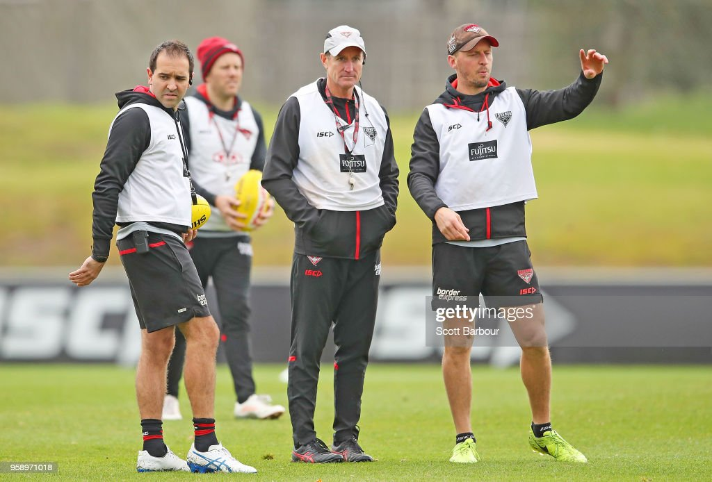 John Worsfold (C), coach of the Bombers looks on as Rob Harding (L), Game Intelligence & Opposition Strategy Coach and James Kelly, (R) Performance Coach gesture during an Essendon Bombers AFL training session at The Hangar on May 16, 2018 in Melbourne, Australia.