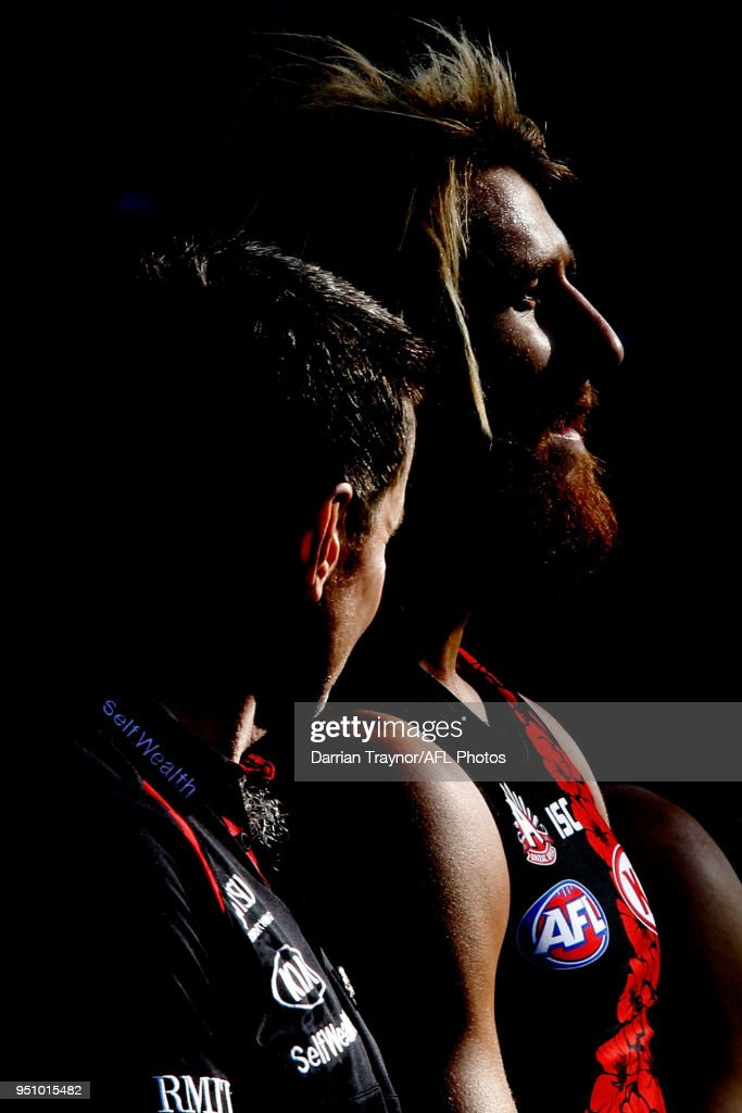 John Worsfold, Senior Coach of the Bombers and captasin Dyson Heppell line up for the playing of the 'Last Post' before the round five AFL match between the Collingwood Magpies and the Essendon Bombvers at Melbourne Cricket Ground on April 25, 2018 in Melbourne, Australia.